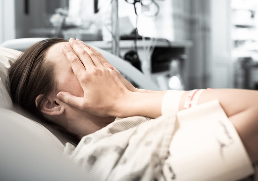 Woman crying in hospital bed
