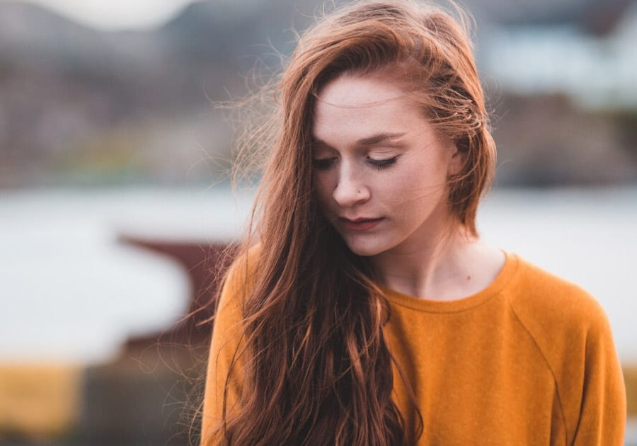 Teenage girl with red hair looking down
