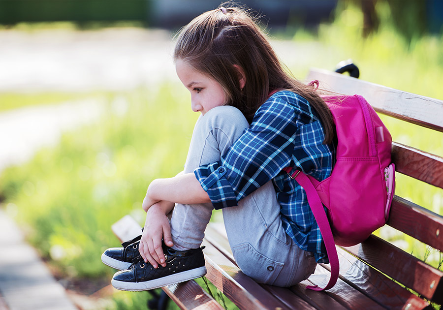 Child sitting on park bench sad