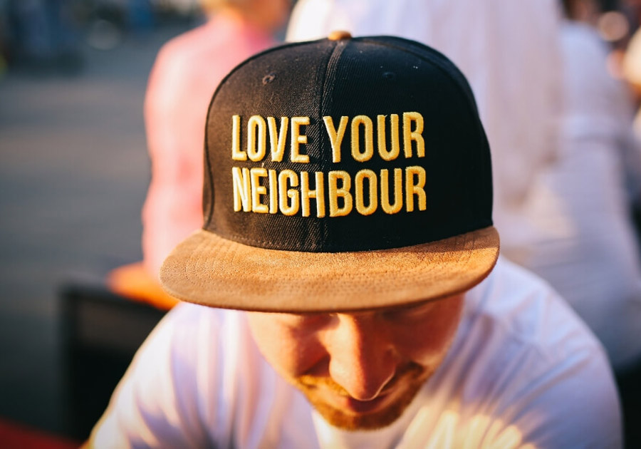 Man wearing Love Your Neighbour cap