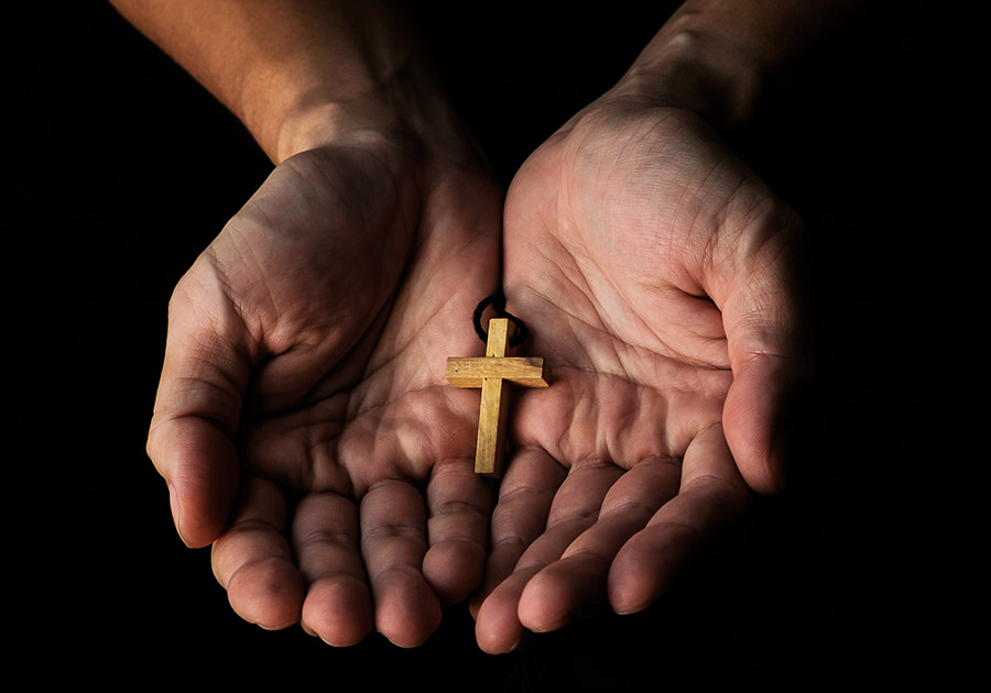 Hands holding a cross