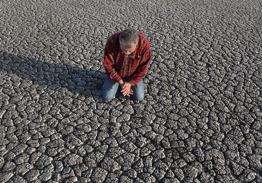 Farmer praying in drought