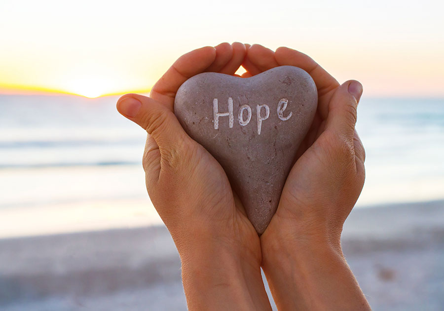 Hands holding heart shaped rock with the words hope