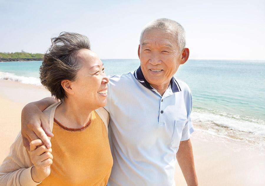 Asian older couple walking on beach