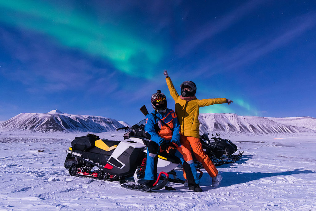 Two people in the artic on snow mobiles
