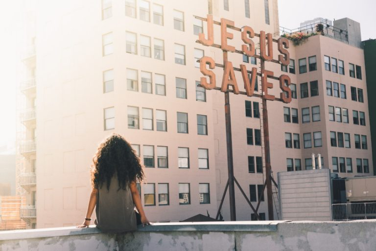 Woman looking at Jesus Saves sign on building