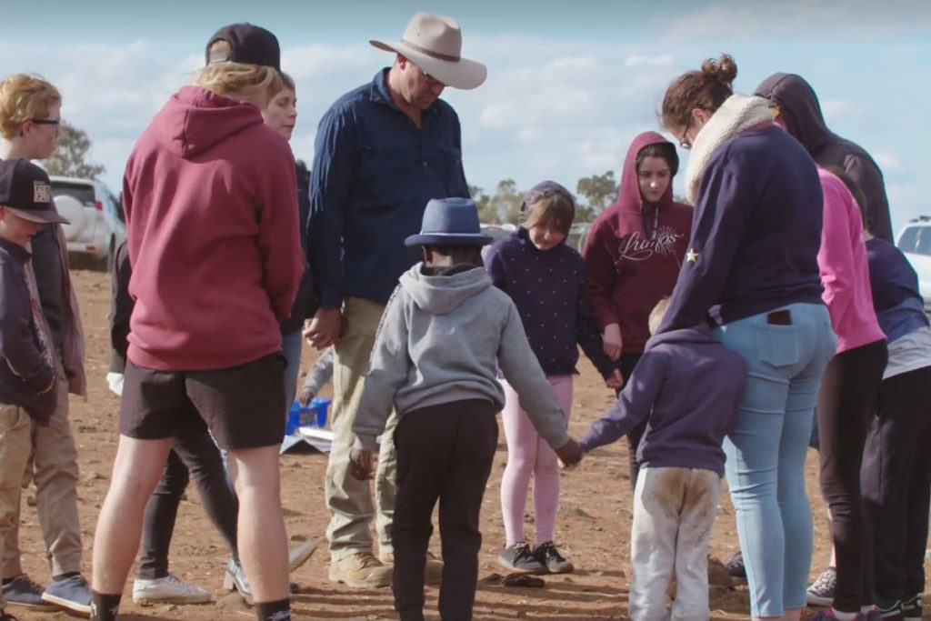 People in the outback praying