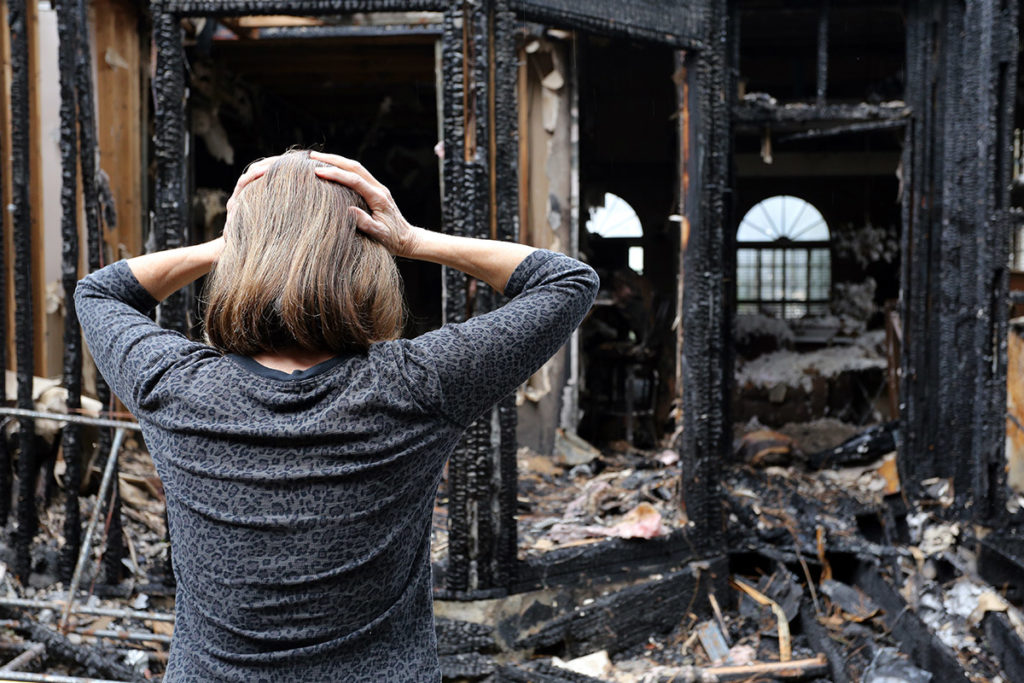 Woman looking at burnt out house
