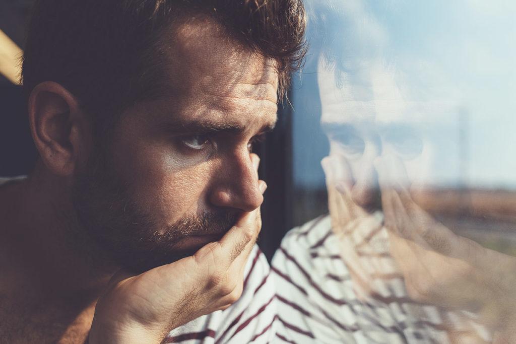 Worried man looking out window