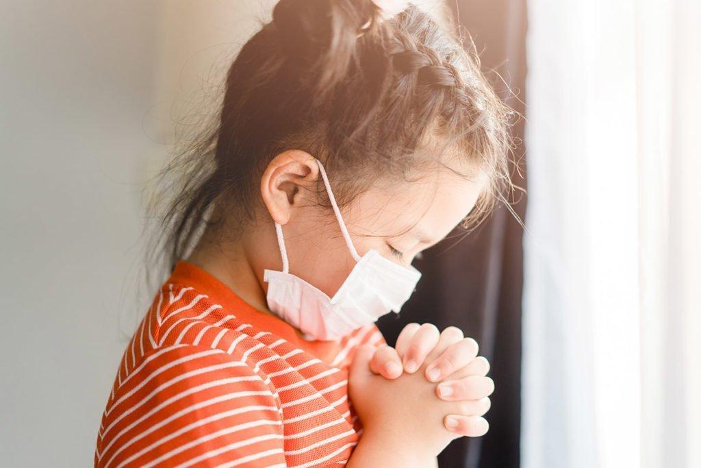 Child praying while wearing mask