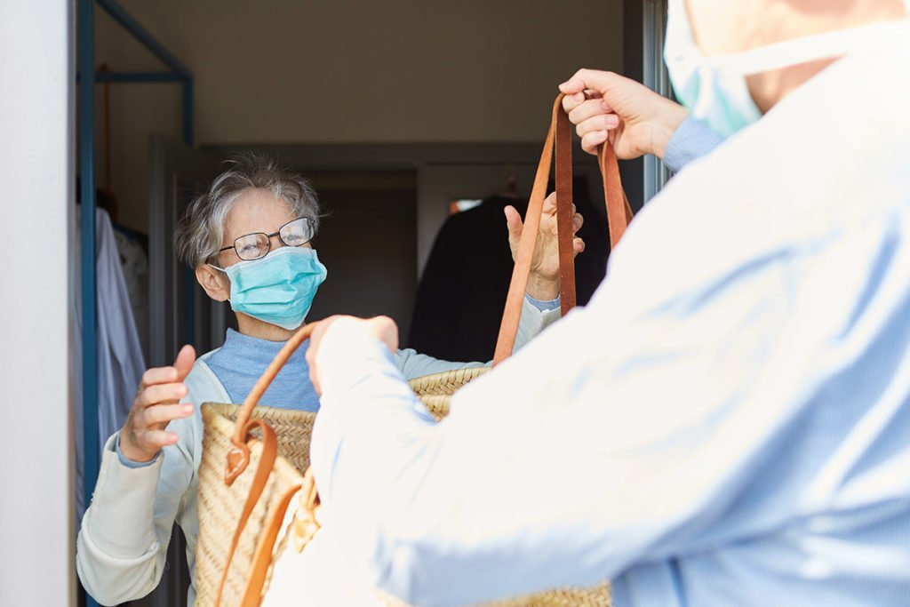 Delivering groceries to elderly woman wearing face mask