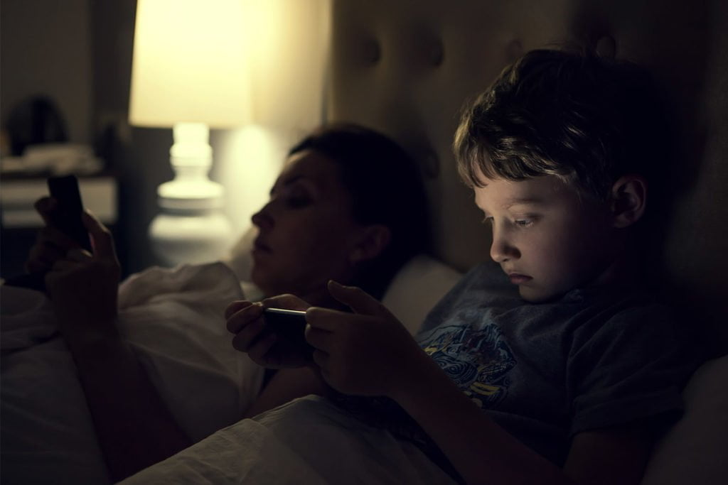 Mother and child looking at pones in bed