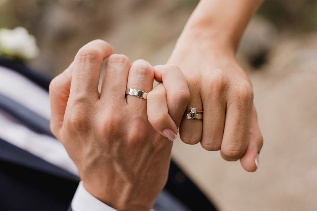 Couple's hands wearing wedding rings