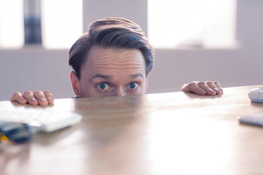 Man looking over desk