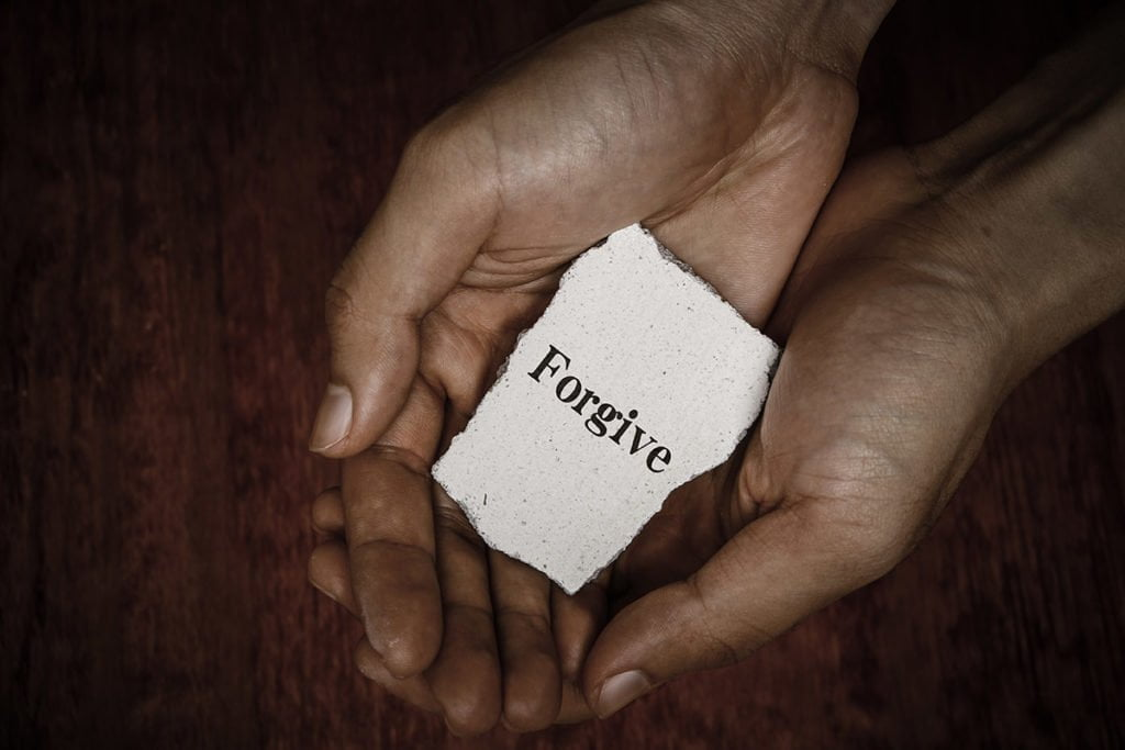 Hands holding forgiveness note