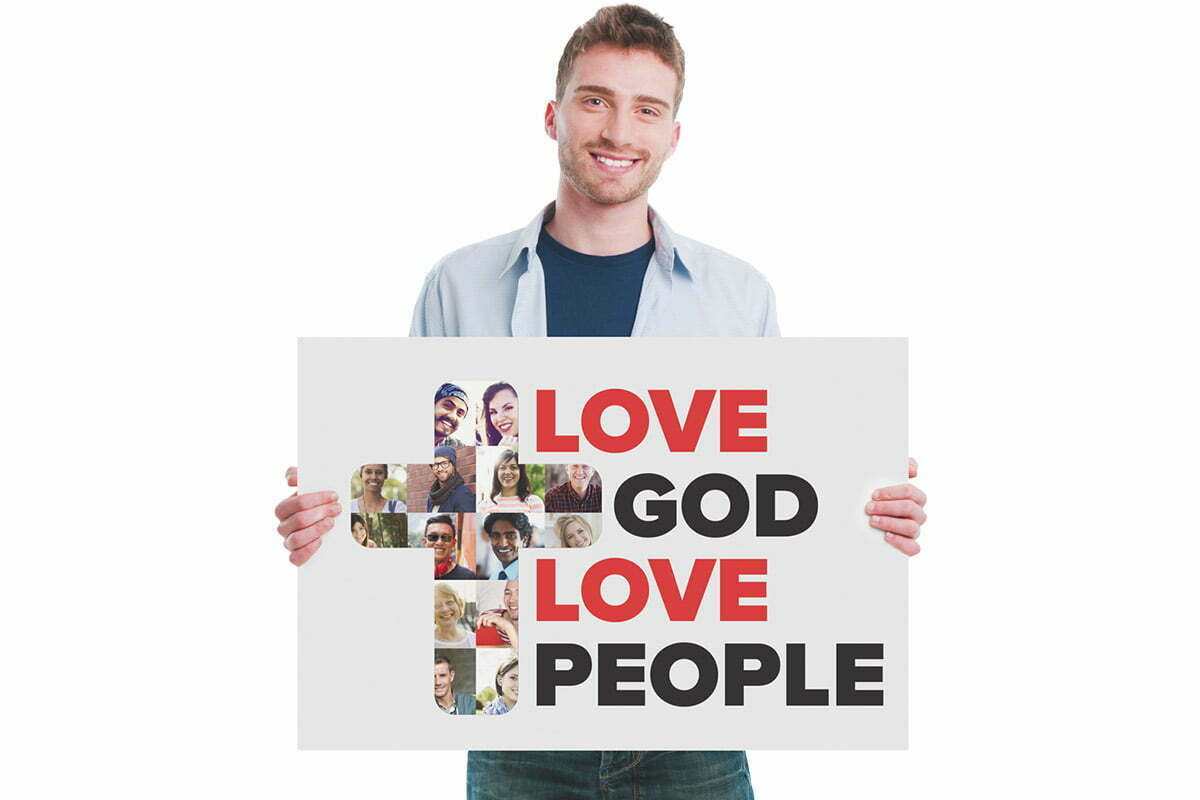 Man holding Love God Love People sign