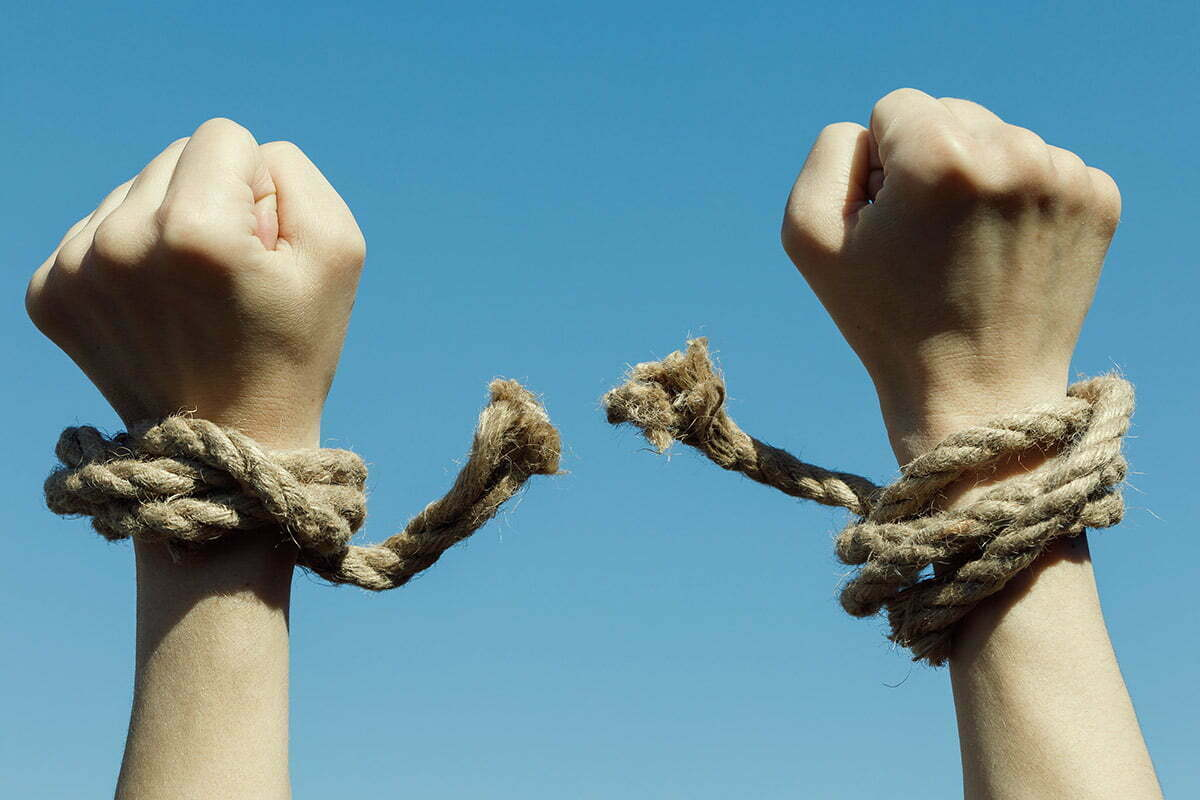 Hands tied in rope breaking free
