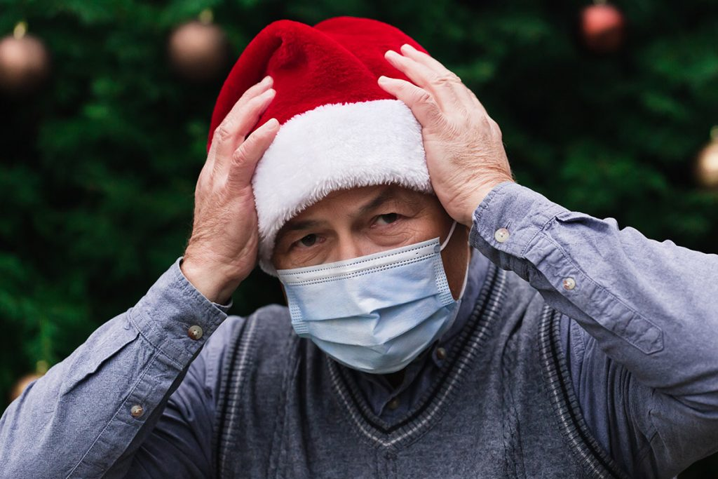 Man confused wearing Christmas hat and mask
