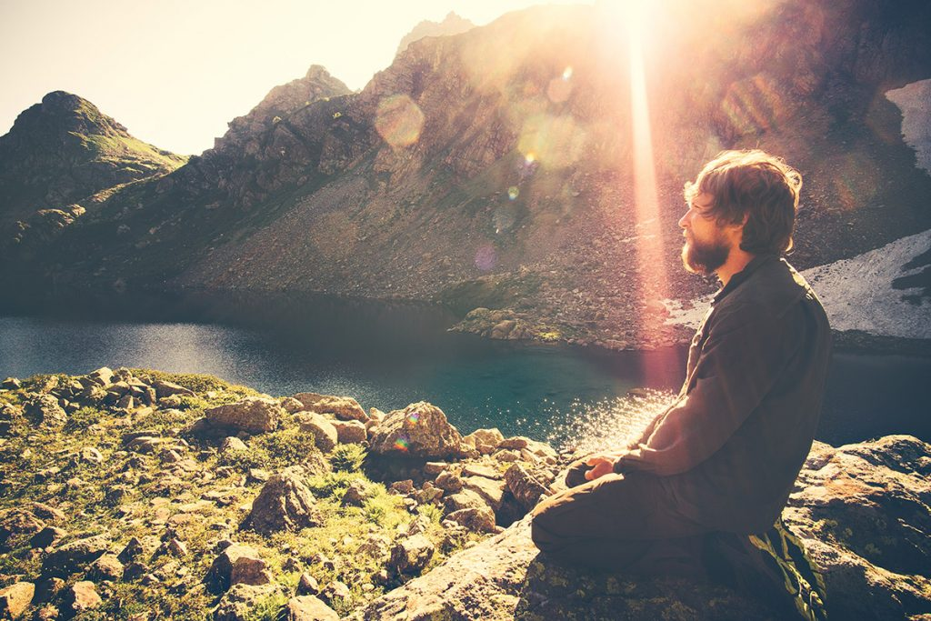 man praying by lake and mountains