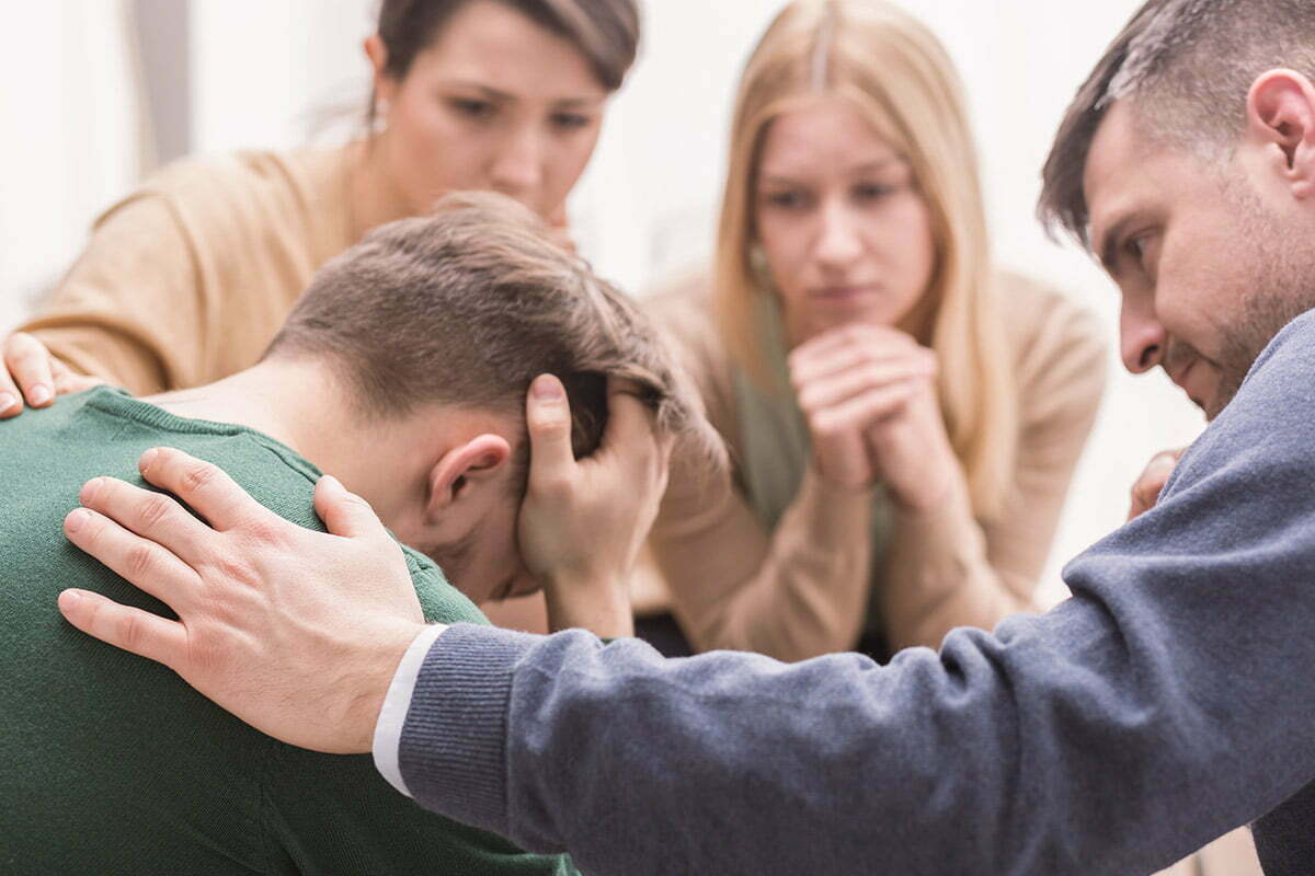 Group praying for young man