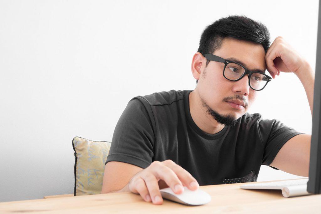 Man bored looking at computer screen