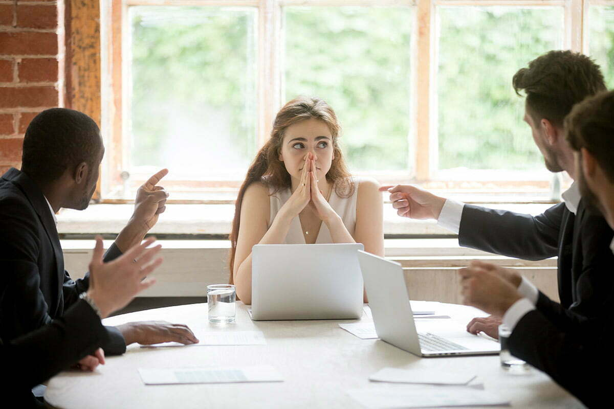 Coworkers bullying woman in meeting