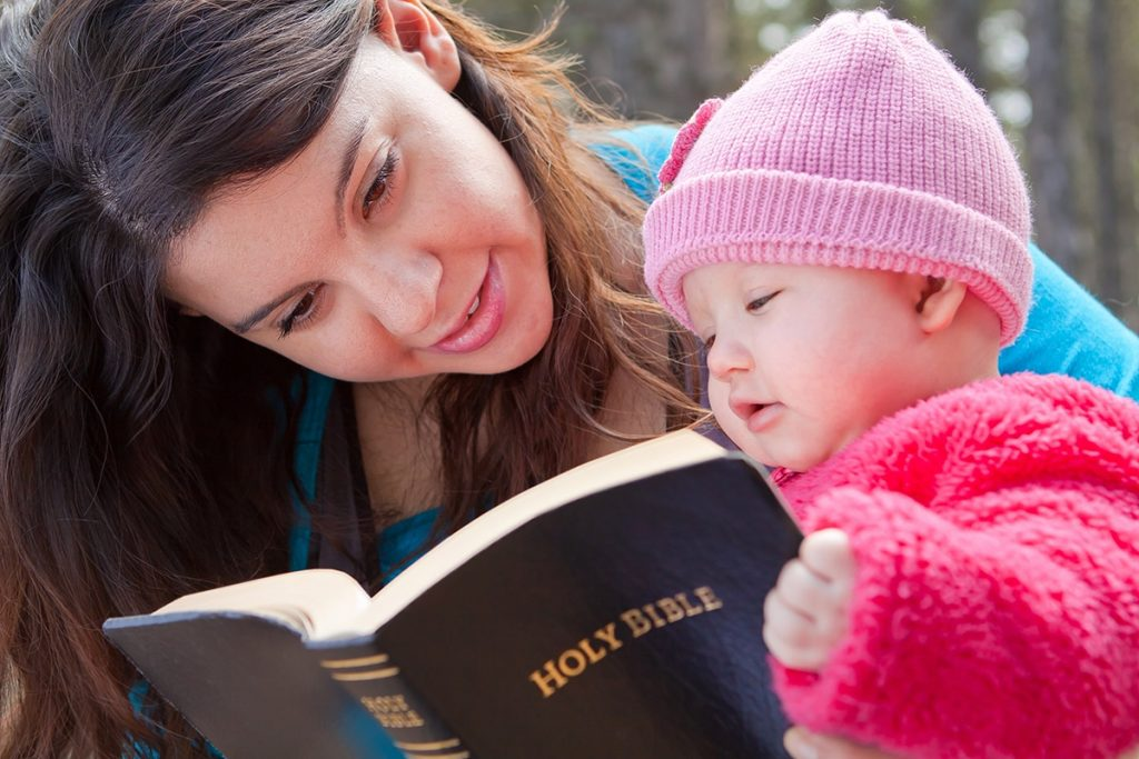 Mum reading Bible to baby