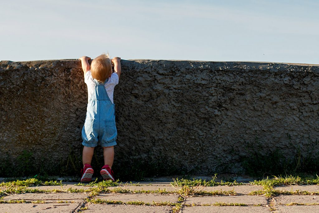 child looking over wall