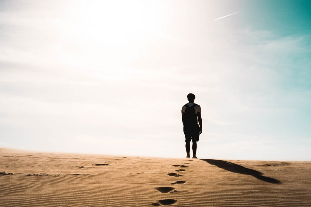 man walking alone in desert