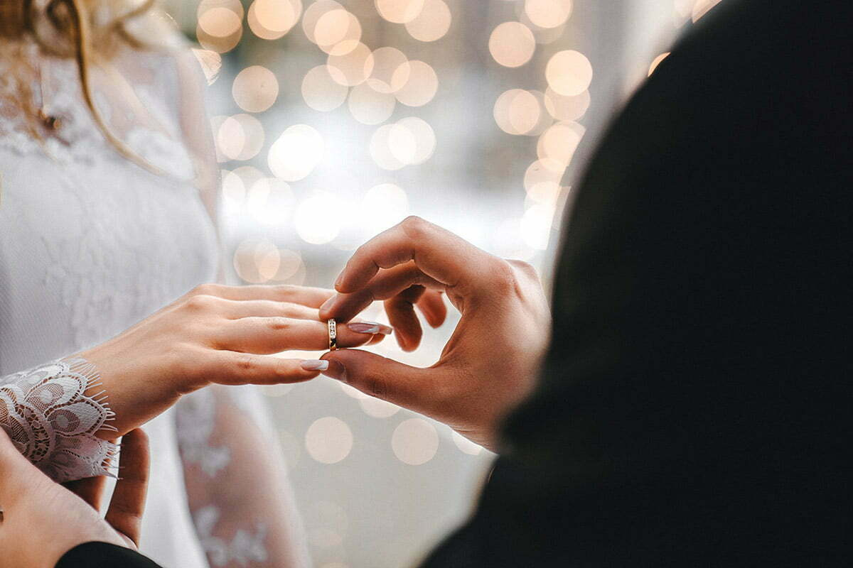 man placing wedding ring on wife
