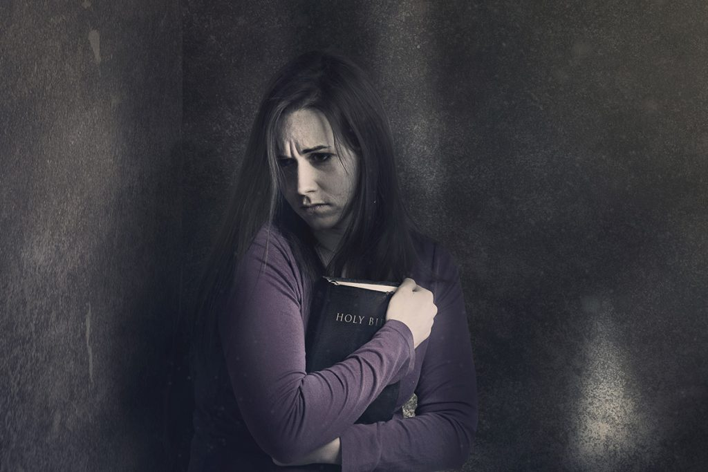Woman in darkness with Bible
