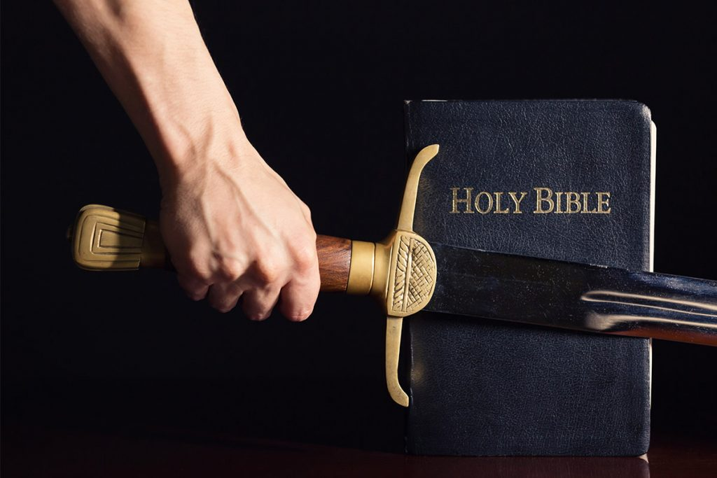 Hand holding sword over bible