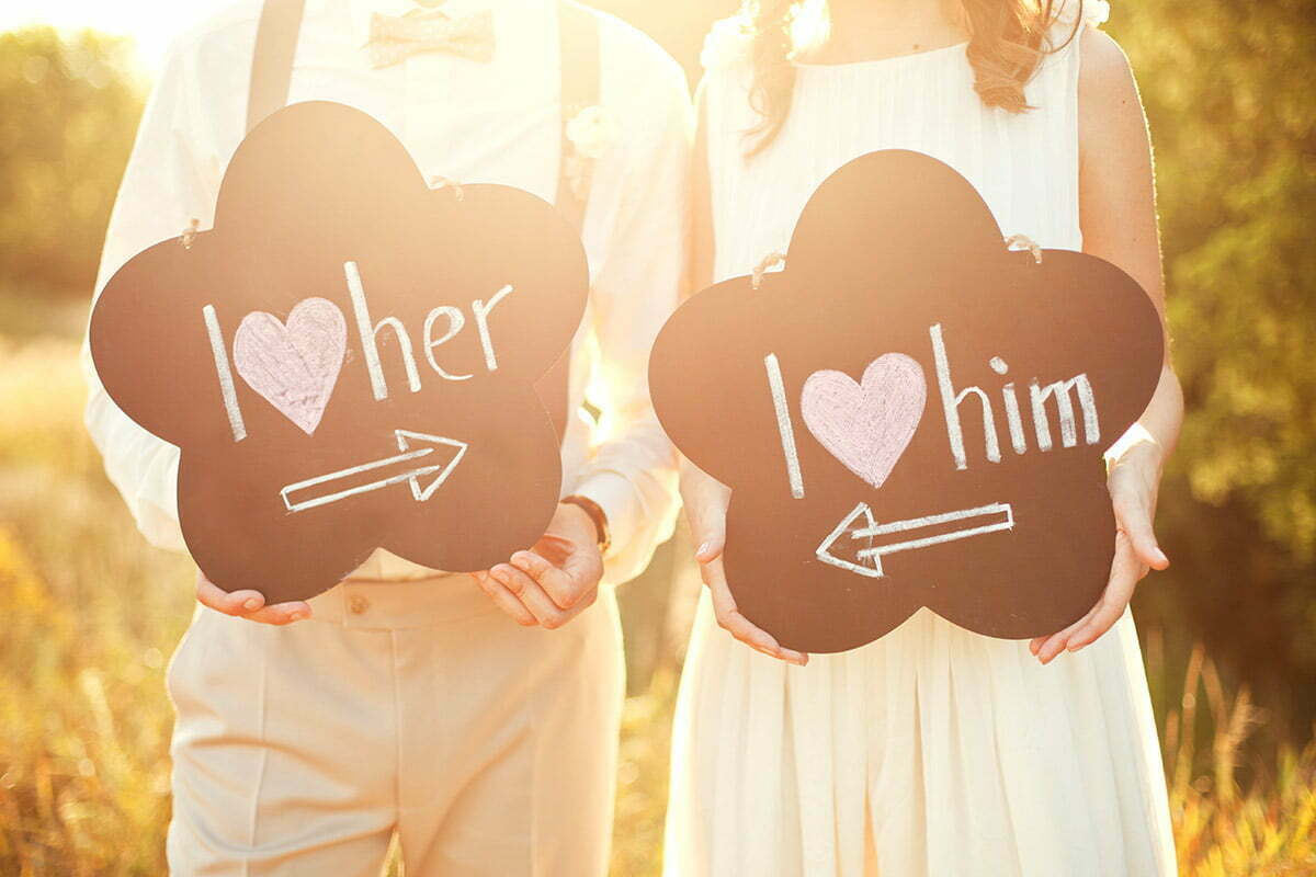 married couple holing love signs