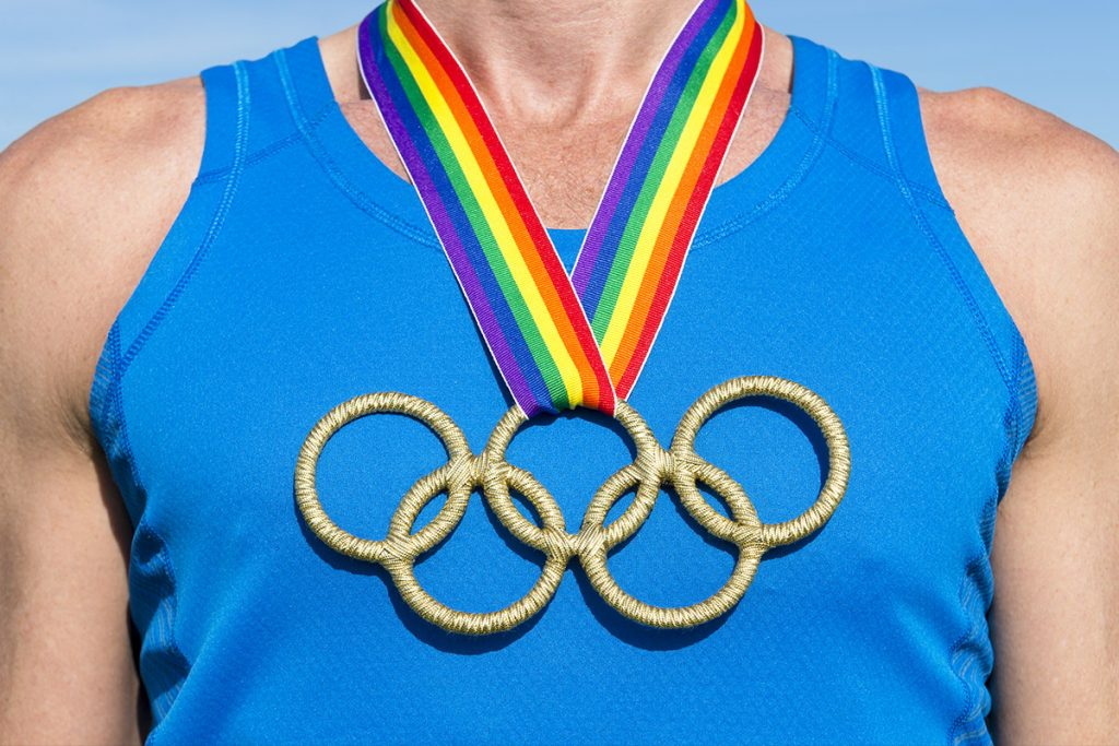 man wearing olympic rings with rainbow ribbon