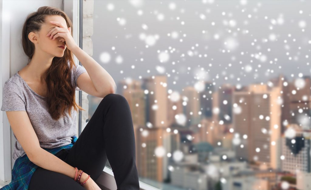 woman sad with snow in window