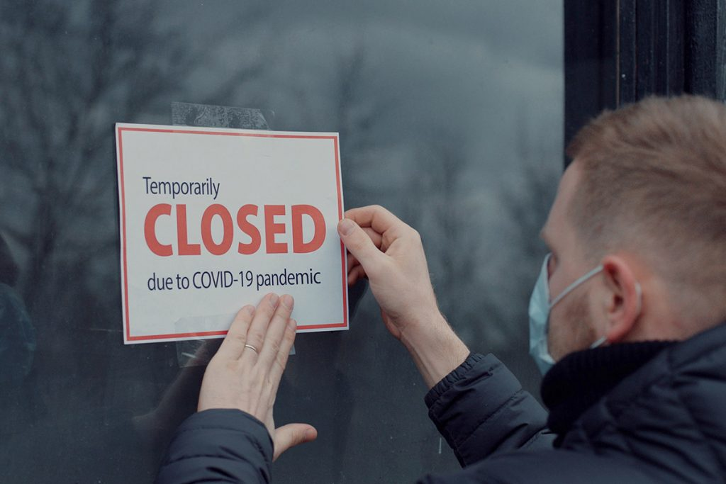 man putting up business closed sign