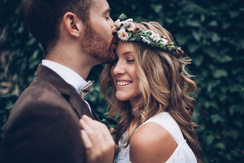 husband kissing wife on wedding day